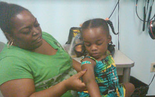 Richee Rogers and her mom admire her bandaid at the back-to-school clinic in the Yonkers District Office